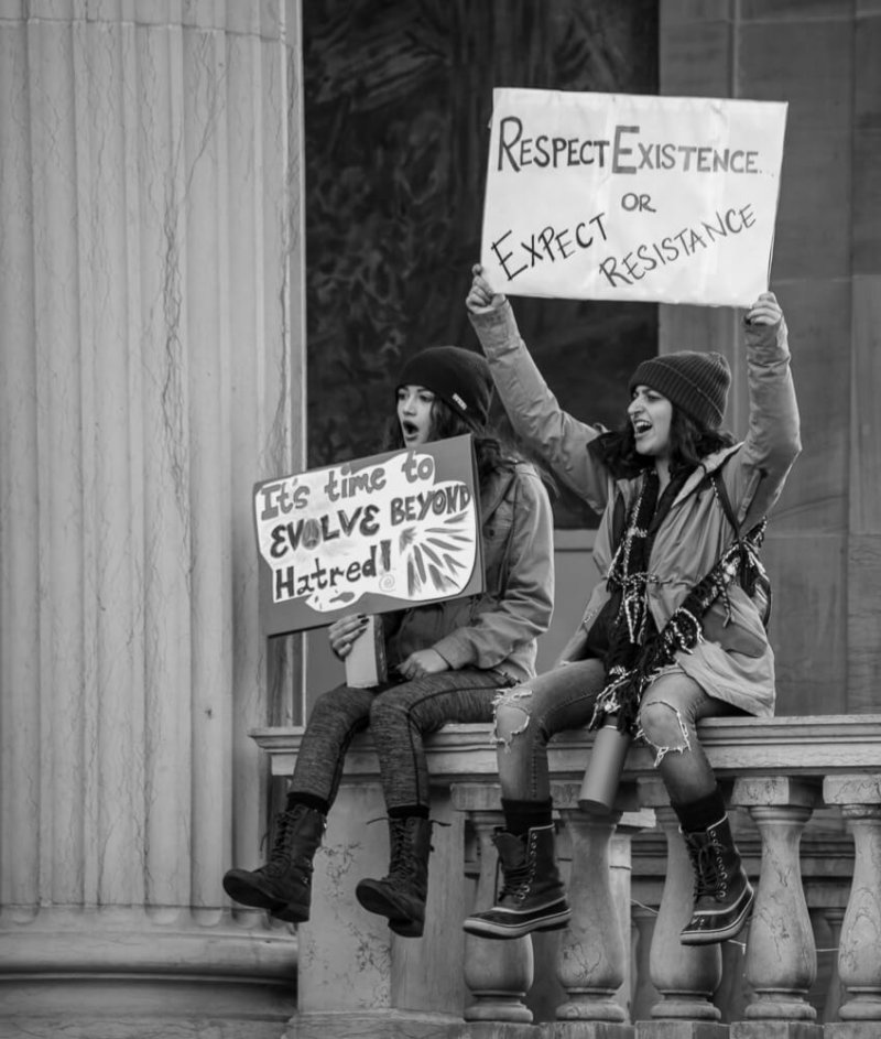 Girls sitting holding signs in black and white.